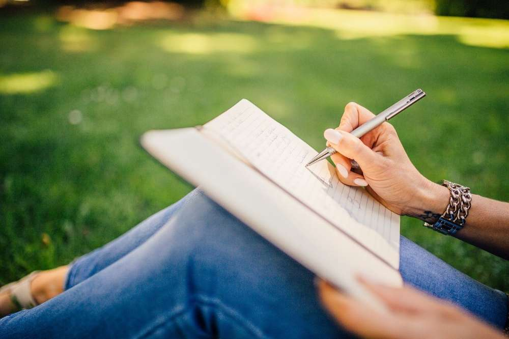 hand writing notepad grass